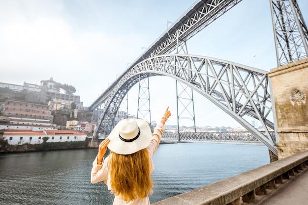 Schöne frau mit hut, die den morgenblick auf die berühmte eisenbrücke während des nebligen wetters in der stadt porto, portugal, genießt