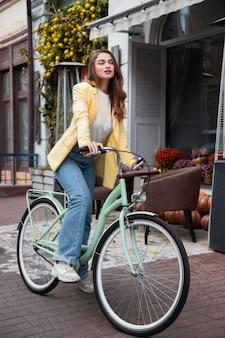 Schöne frau mit ihrem fahrrad auf der straße