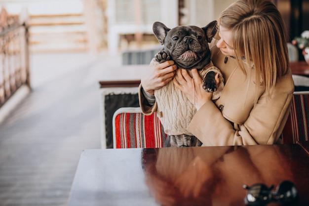 Schöne frau mit ihrer netten französischen bulldogge in der warmen ausstattung