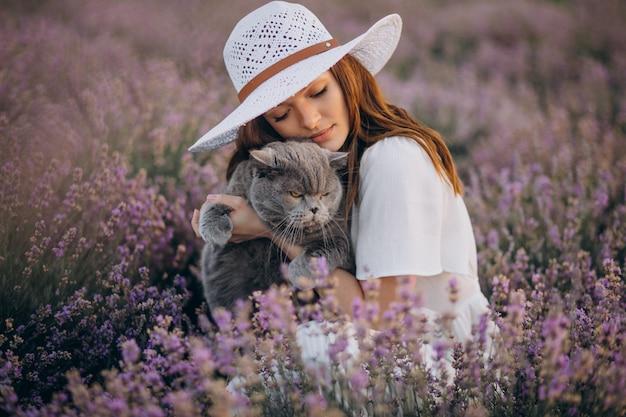 Schöne frau mit katze in einem lavendelfeld