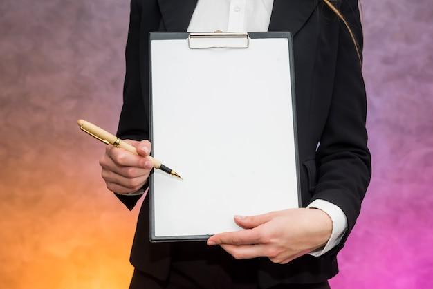 Schöne frau mit klemmbrett angebot unterzeichnen einen vertrag mit stift
