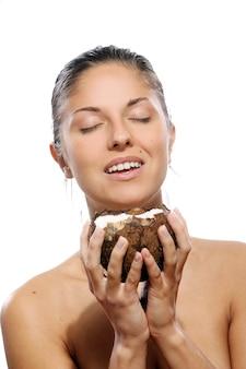 Schöne frau mit kokosnuss in den händen