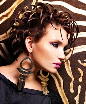 Schöne frau mit kreativer modefrisur und glamour-make-up-aufstellung.