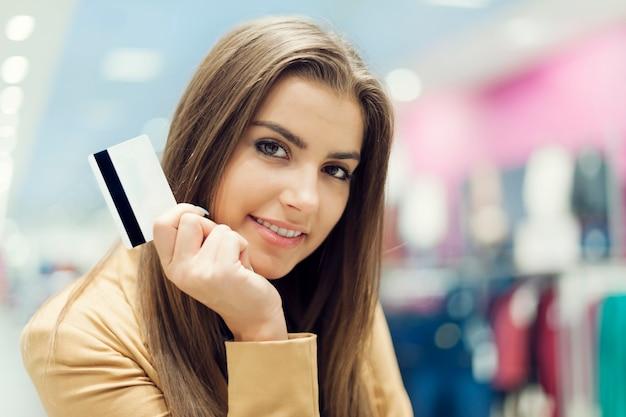 Schöne frau mit kreditkarte im einkaufszentrum
