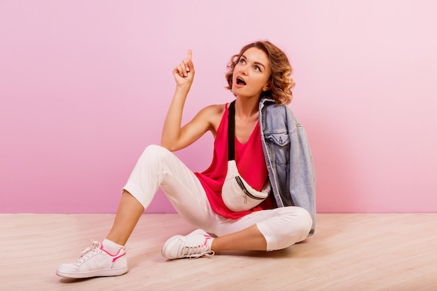 Schöne frau mit kurzen gewellten haaren, die auf dem boden über rosa sitzen