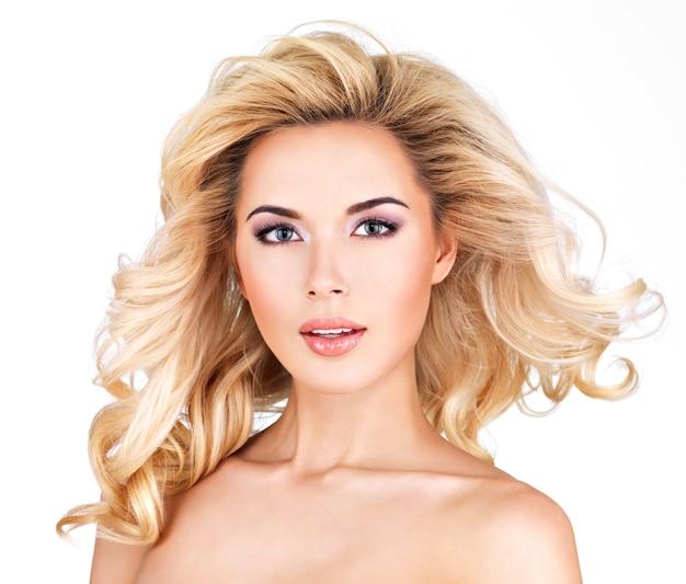 Schöne frau mit langen blonden lockigen haaren
