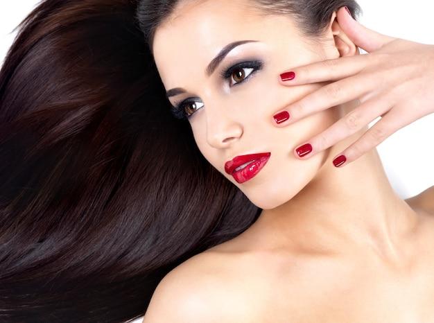 Schöne frau mit langen braunen geraden haaren und roten nägeln der eleganz