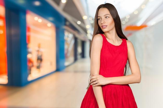 Schöne frau mit langen braunen haaren im roten kleid