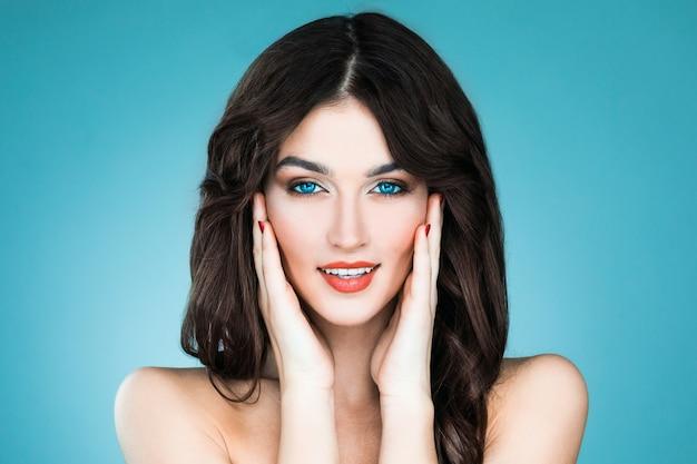 Schöne frau mit langen braunen haaren. nahaufnahme-schönheitsporträt eines mode-modells, das auf der blauen wand aufwirft