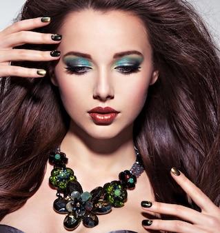 Schöne frau mit langen braunen haaren, türkisfarbenem make-up und nägeln