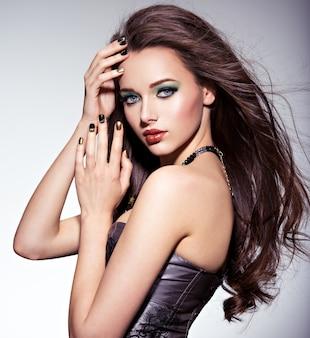 Schöne frau mit langen braunen haaren und grünem make-up und nägeln
