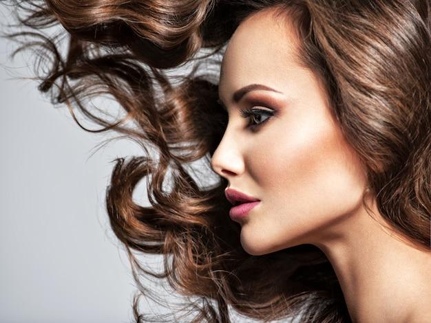 Schöne frau mit langen braunen lockigen haaren. profilporträt eines hübschen jungen mädchens mit fliegenden haaren