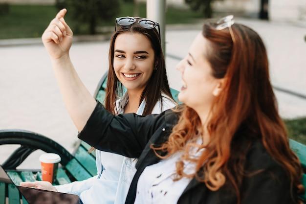 Schöne frau mit langen dunklen haaren lächelnd, während sie ihre freundin geschichte hört, während im park auf einer bank sitzt.