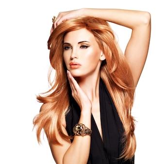 Schöne frau mit langen geraden roten haaren in einem schwarzen kleid, das ihr gesicht berührt. model posiert. auf weiß isoliert