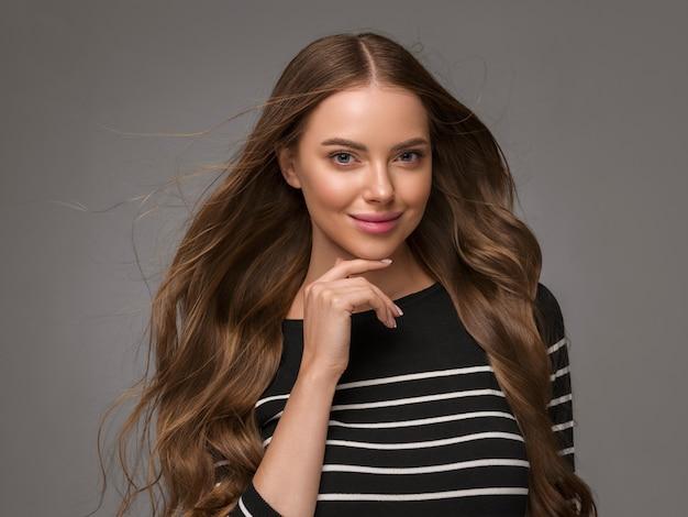 Schöne frau mit langen, gesunden, lockigen haaren im lässigen gestreiften pullover. farbiger hintergrund.