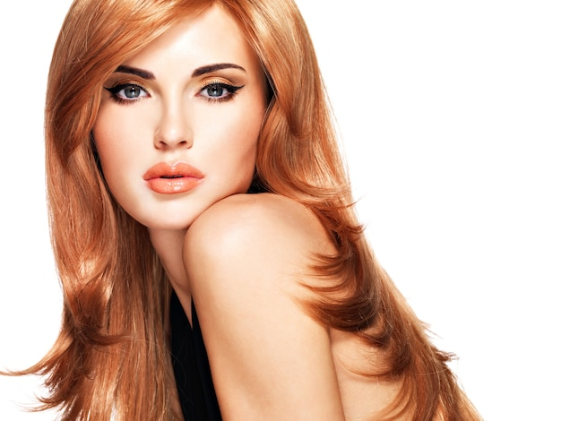 Schöne frau mit langen glatten roten haaren in einem schwarzen kleid. model posiert. auf weiß isoliert