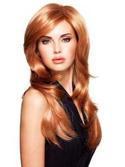 Schöne frau mit langen glatten roten haaren in einem schwarzen kleid