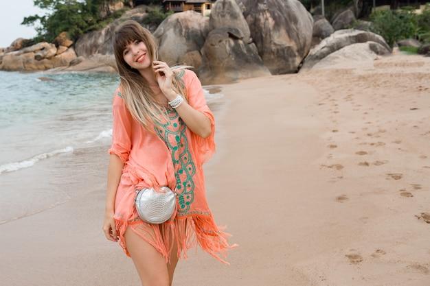 Schöne frau mit langen haaren im stilvollen boho-sommerkleid, das im tropischen strand aufwirft.