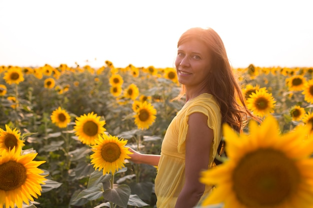 Schöne frau mit langen haaren im weißen kleid auf einem sonnenblumenfeld im sommer im sonnenlicht