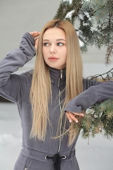 Schöne frau mit langen haaren posiert im winter im wald