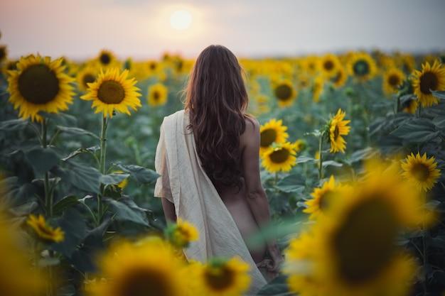 Schöne frau mit langen haaren sexy rücken in einem sonnenblumenfeld im sommer im sonnenlicht