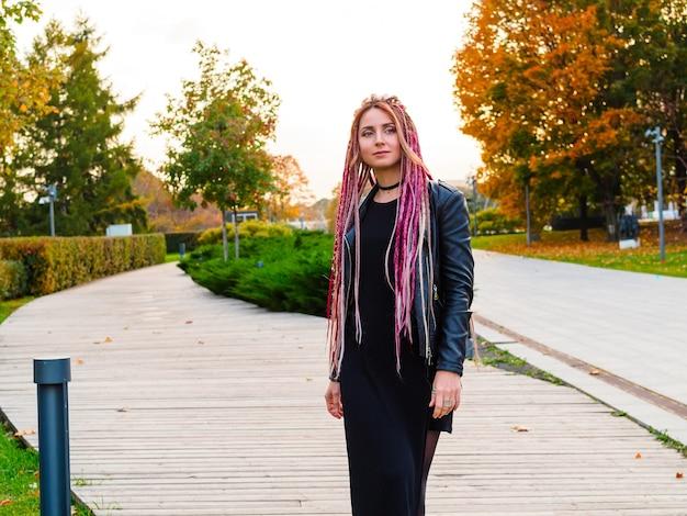 Schöne frau mit langen rosa haaren in schwarzer kleidung geht im herbst im park spazieren und schaut zur seite