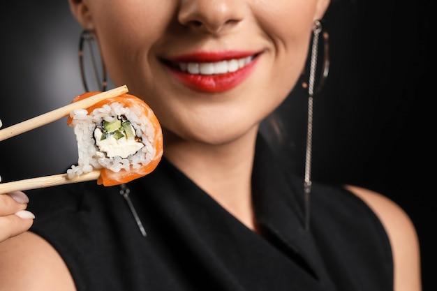 Schöne frau mit leckerem sushi auf dunklem hintergrund, nahaufnahme