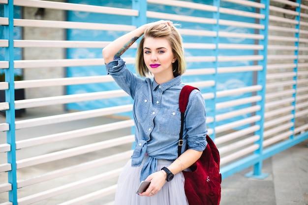 Schöne frau mit leuchtend rosa lippen, die ihre haare mit einer hand und smartphone mit einer anderen hand halten