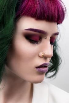 Schöne frau mit lila grünem professionell gefärbtem haar