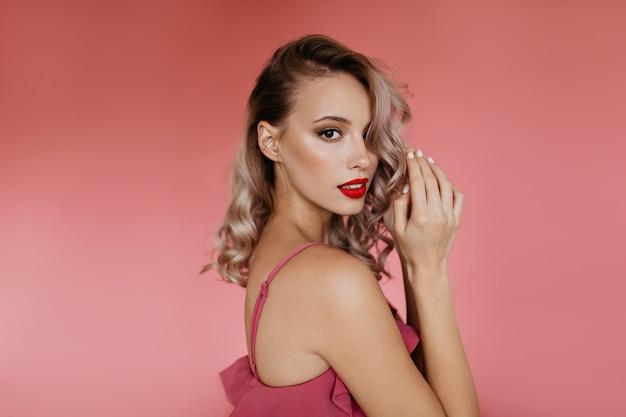Schöne frau mit lockigem blondem haar, unter einer seite gerafft und mit hellem make-up auf vollen lippen schaut mit gefalteten handflächen nach vorne