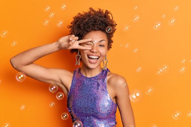 Schöne frau mit lockigem haar lächelt breit gekleidet auf lila hemd kommt auf disco-party macht v-zeichen isoliert über orange wand fliegende seifenblasen bleibt immer positiv
