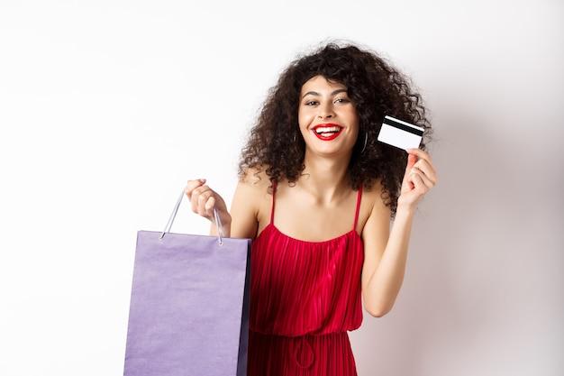 Schöne frau mit lockigem haar, rotes kleid, einkaufstasche und plastikkreditkarte, weißer hintergrund zeigend.