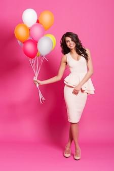 Schöne frau mit luftballons auf rosa