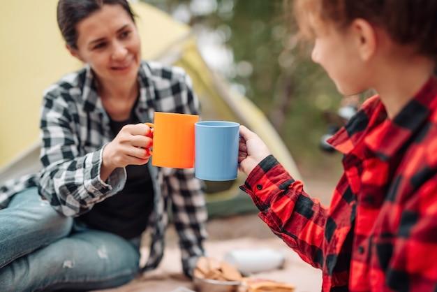 Schöne frau mit mädchen trinkt tee beim camping im wald mit zelt