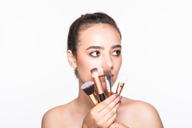 Schöne frau mit make-up-bürsten nahe ihrem gesicht lokalisiert auf weißer wand