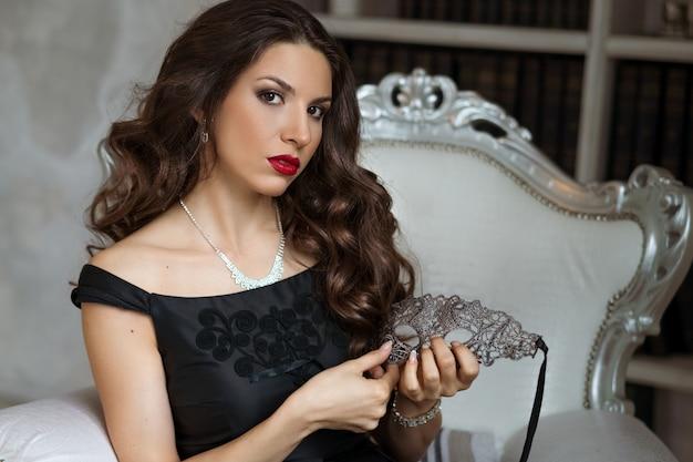 Schöne frau mit make-up im schwarzen kleid mit einer maske in der hand sitzt auf einem stuhl