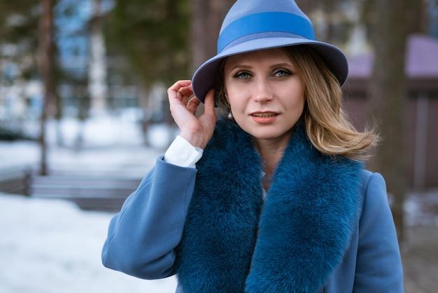 Schöne frau mit make-up, in einem blauen mantel und in einem hut, der in der natur auf dem schnee aufwirft
