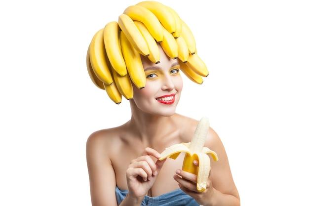Schöne frau mit make-up und bananen auf dem kopf, die banane schälen. studioaufnahme