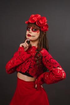 Schöne frau mit make-up und dia de los muertos-kleidung auf schwarzem hintergrund.