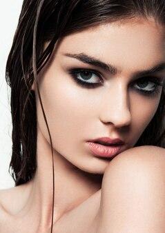 Schöne frau mit make-up und nassen haaren mit rauchigen augen und roten lippen