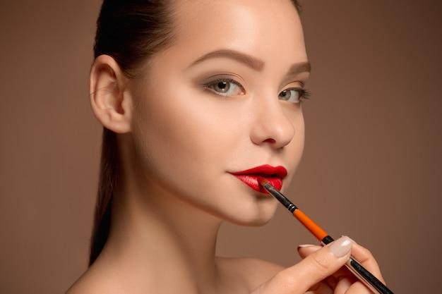 Schöne frau mit make-up und pinsel