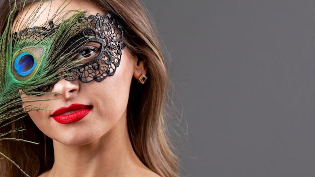 Schöne frau mit maske und pfauenfeder