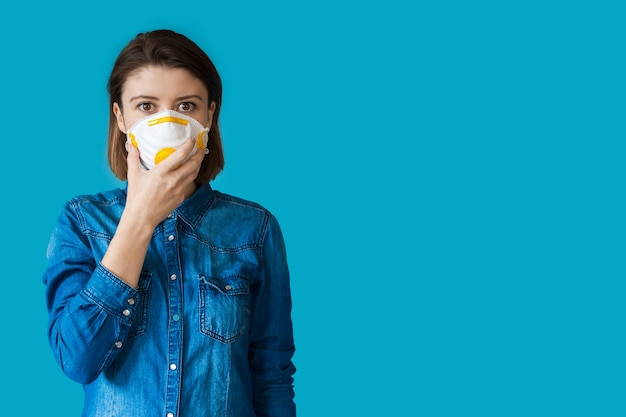 Schöne frau mit medizinischer maske und braunen haaren, die in einem jeanshemd auf einer blauen wand mit leerzeichen aufwerfen