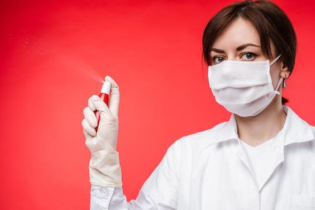 Schöne frau mit medizinischer maske verbreitet antiseptikum in der luft, bild lokalisiert auf rotem hintergrund
