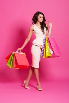Schöne frau mit mehrfarbigen einkaufstaschen