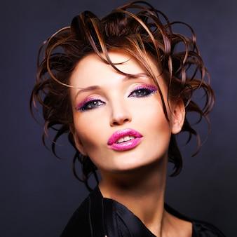 Schöne frau mit modefrisur und leuchtend rosa lippen posierend.