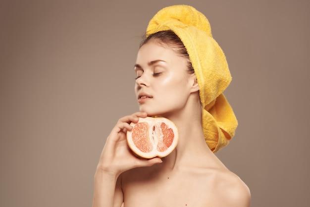 Schöne frau mit nacktem körper mit fruchtvitaminen, die nahaufnahme aufwerfen