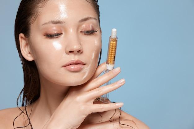 Schöne frau mit nassem gesicht, das kosmetikinjektion hält
