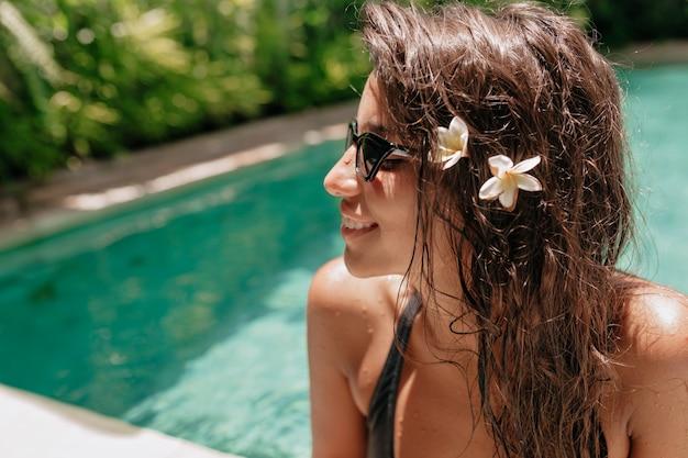 Schöne frau mit nassen langen haaren im schwimmbad. gebräuntes europäisches mädchen, herrliches gesicht, das sommer an heißem tag auf tropischem resort genießt