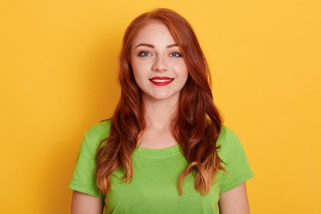 Schöne frau mit natürlichem lächelndem gesicht mit roten lippen, grünes t-shirt tragend